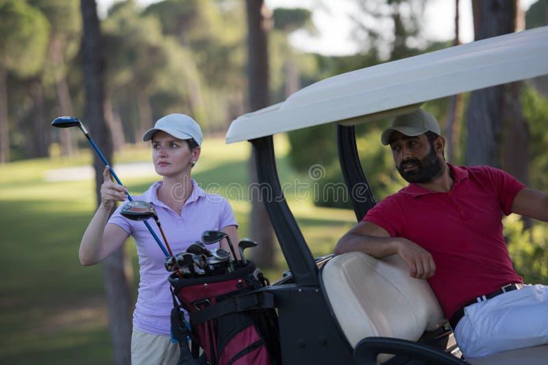 Par i barnvagn på golfbana royaltyfri foto
