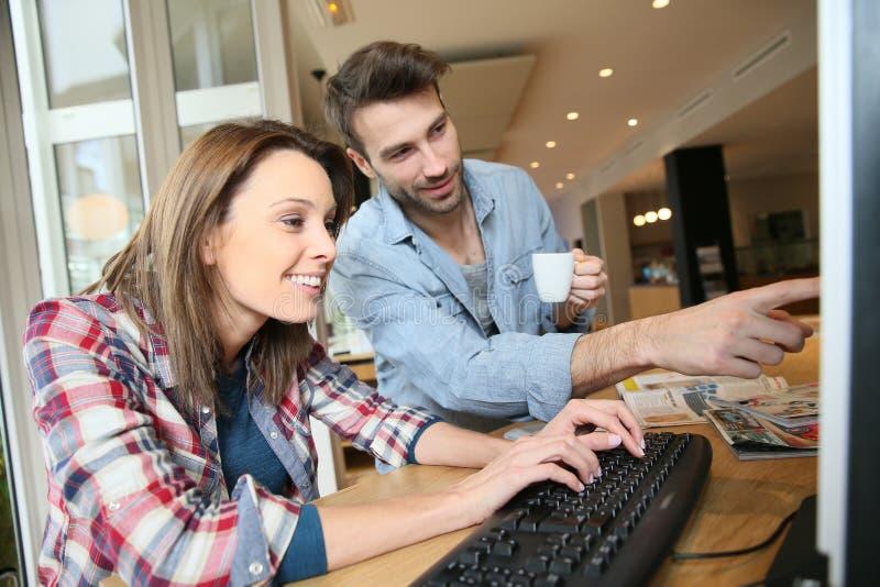 Par i en cybercafe som websurfing royaltyfria bilder