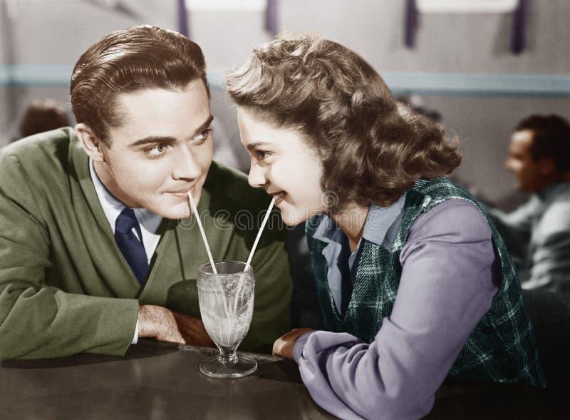 Par i en restaurang som ser de och delar en milkshake med två sugrör (alla visade personer inte är längre uppehälle fotografering för bildbyråer