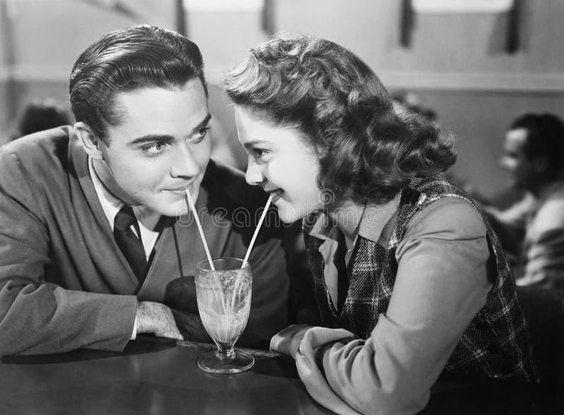 Par i en restaurang som ser de och delar en milkshake med två sugrör (alla visade personer inte är längre uppehälle royaltyfri bild