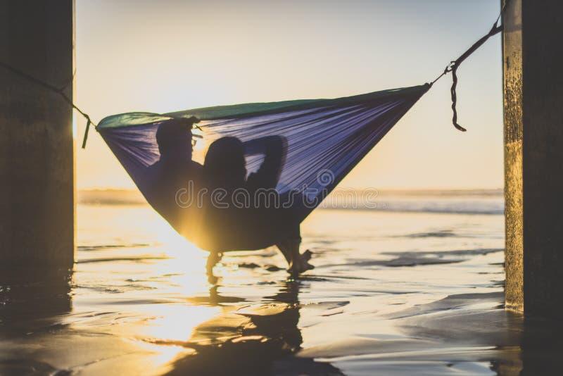 Par i hängmattan som håller ögonen på solnedgången fotografering för bildbyråer