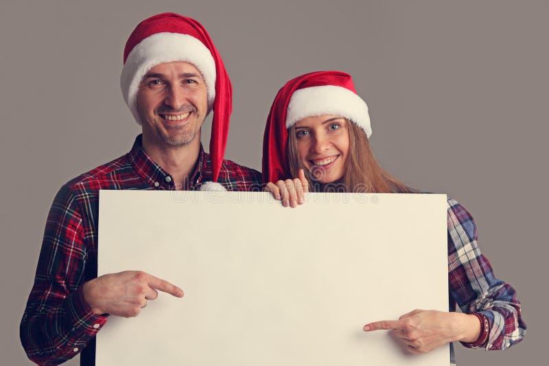 Par i jultomtenhattar med banret fotografering för bildbyråer