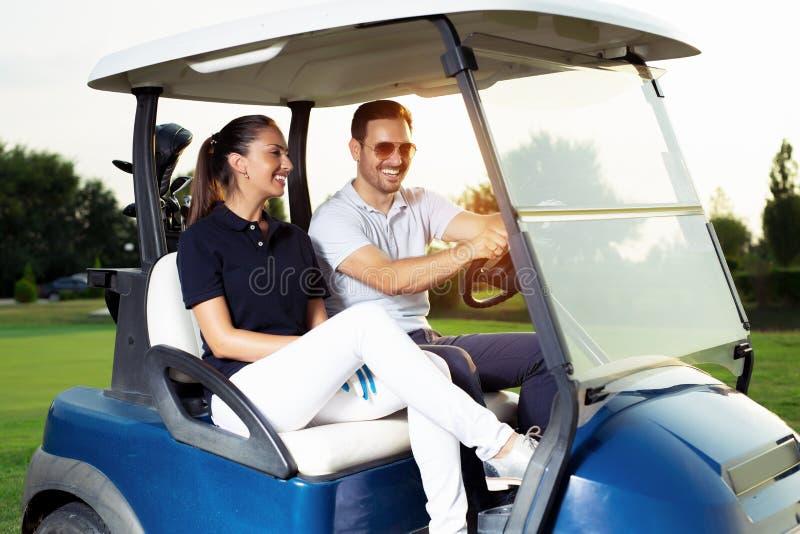 Par, i körning av barnvagnen på golfbana royaltyfria bilder