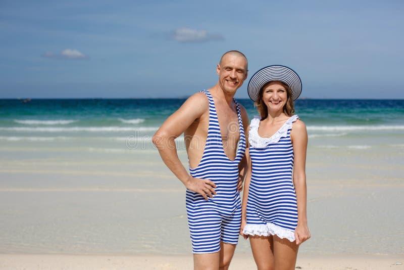 Par i retro baddräkt på stranden arkivbild