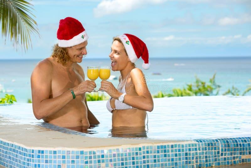 Par i simbassängen som rostar för jul royaltyfri foto