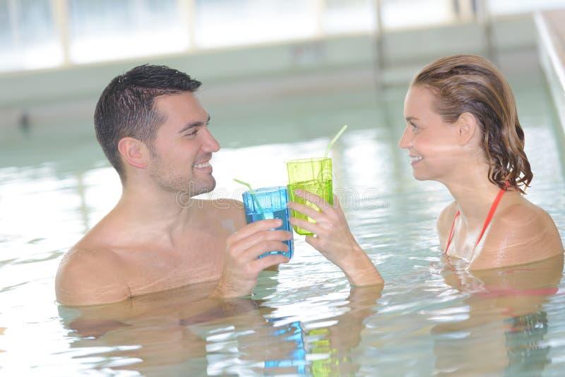 Par i simbassängen som rostar med coctailar arkivfoto