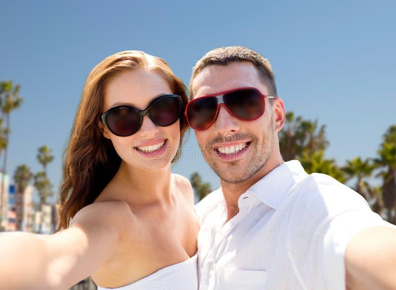 Par i skuggor som gör selfie över den venice stranden royaltyfri foto