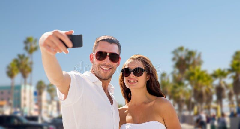 Par i skuggor som gör selfie över den venice stranden fotografering för bildbyråer