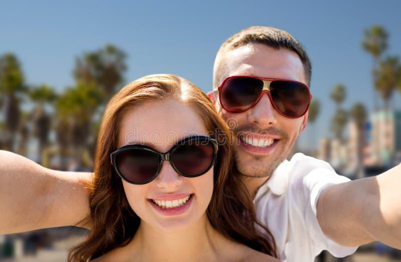 Par i skuggor som gör selfie över den venice stranden royaltyfria bilder