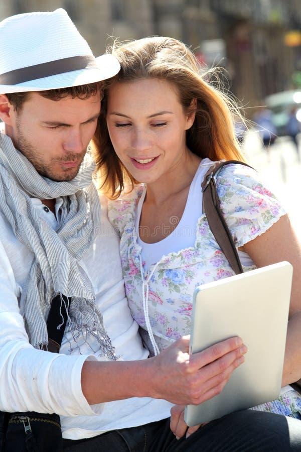 Par i staden som websurfing på minnestavlan royaltyfri bild