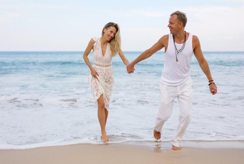 Par i tillfällig sommarkläder som har gyckel i havvatten royaltyfria foton