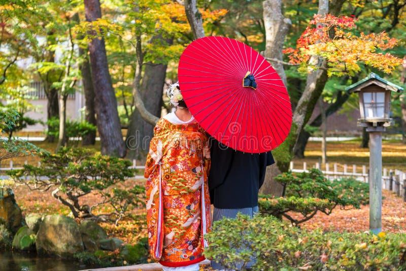 Par i traditionell kl?nning under det traditionella paraplyet, Kenrokuen tr?dg?rd, Kanazawa royaltyfri foto