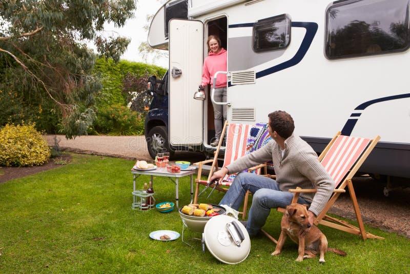 Par i Van Enjoying Barbeque On Camping ferie fotografering för bildbyråer