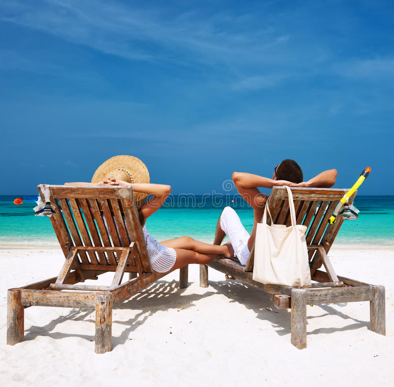 Par i vit kopplar av på en strand på Maldiverna fotografering för bildbyråer
