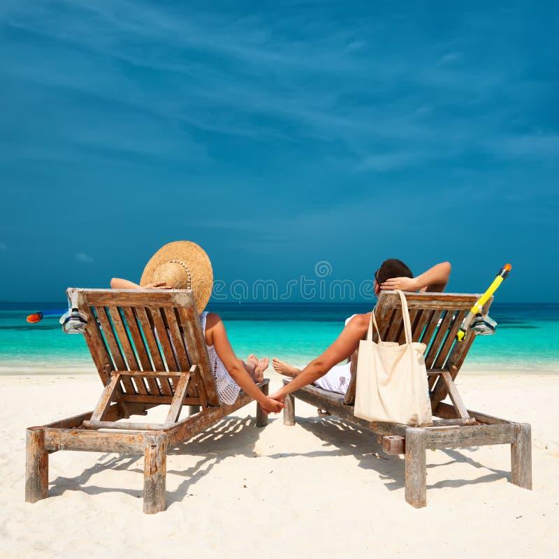 Par i vit kopplar av på en strand på Maldiverna royaltyfri fotografi