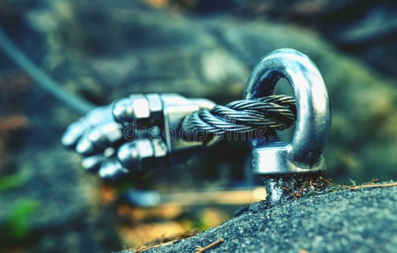 Par l'intermédiaire de la corde en acier de ferrata sur un détail de roche Ancre en acier de chrome photo stock