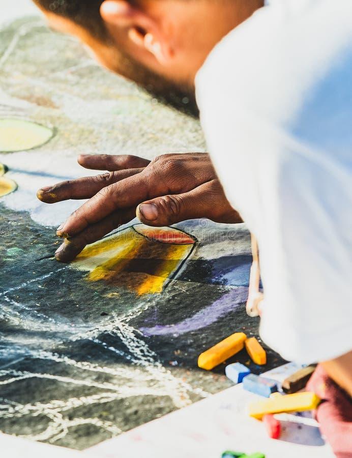 Par l'intermédiaire des Arte-artistes créant l'art de craie sur des rues photos stock