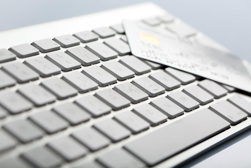 Par la carte de crédit sur un clavier d'ordinateur photos stock