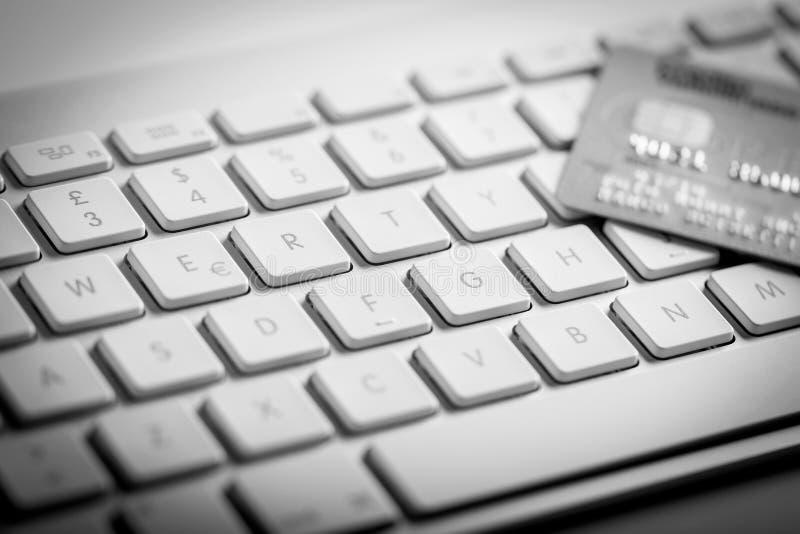 Par la carte de crédit sur un clavier d'ordinateur photographie stock libre de droits