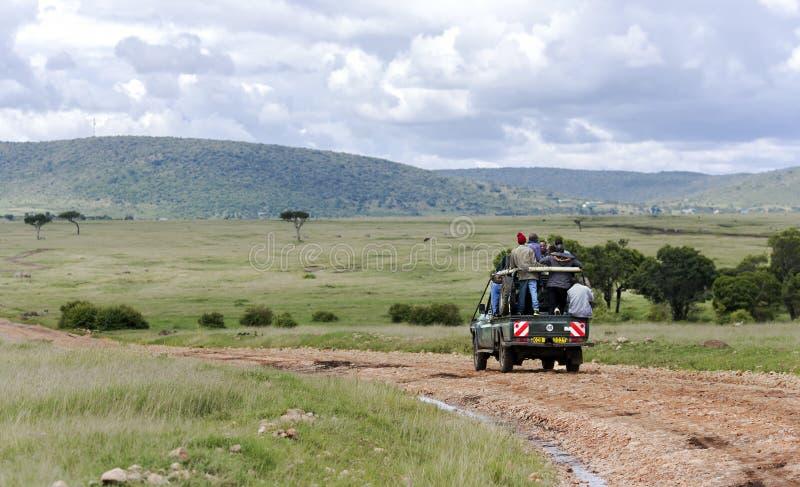 Par le masai Mara National Park Jeep porte les résidents africains locaux image stock
