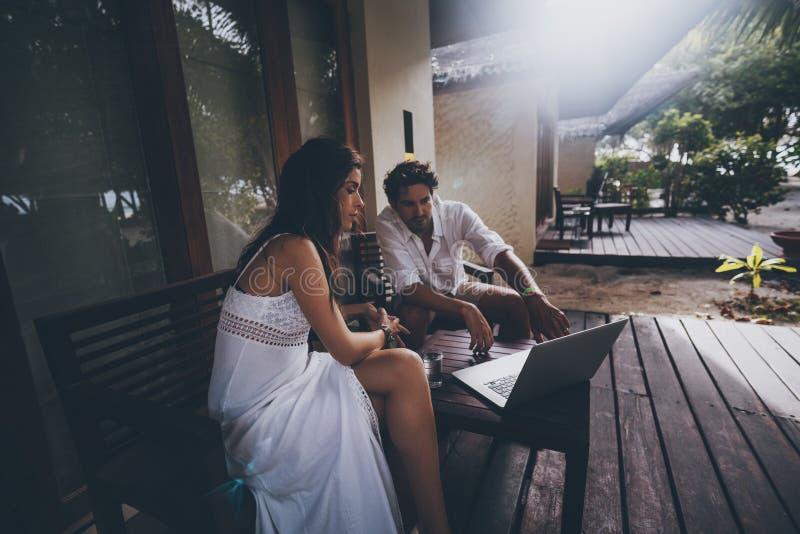 Par: man och kvinna med bärbara datorn på verandan arkivfoto