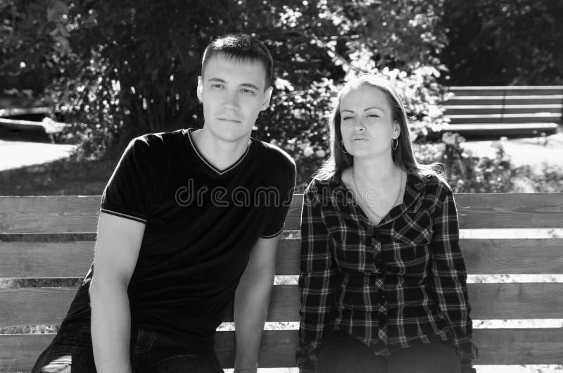 Par man och kvinnasammanträde på bänk med ett eftertänksamt och en anxiou royaltyfria bilder