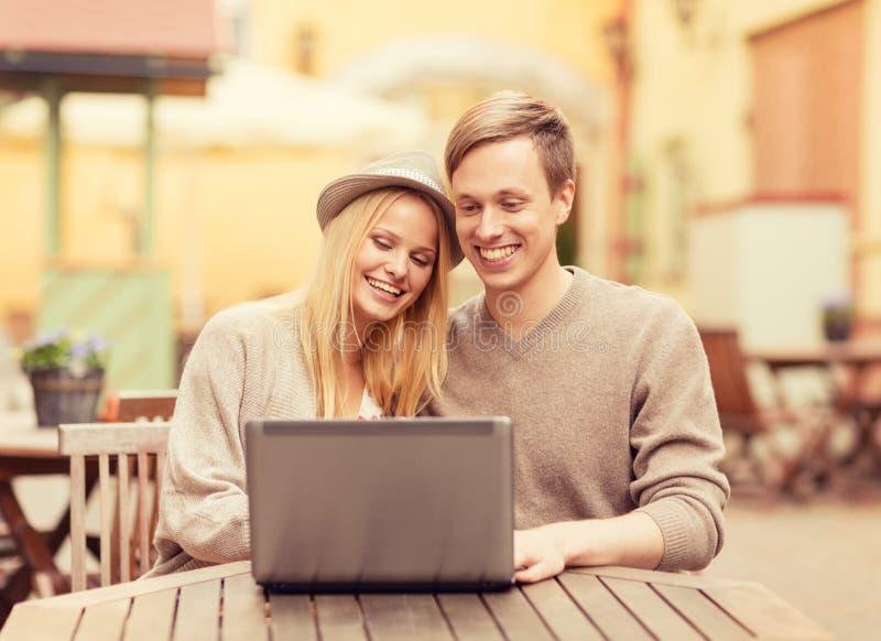 Par med bärbara datorn i kafé arkivfoto