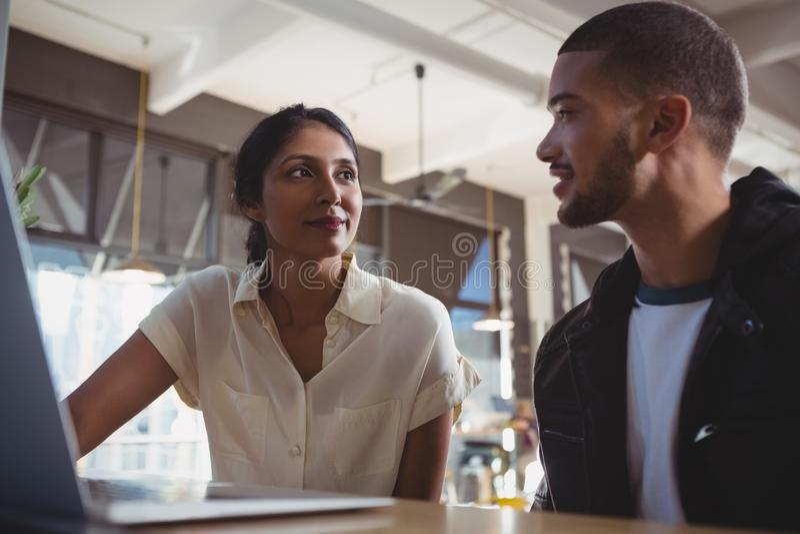 Par med bärbara datorn som ser sig i kafé royaltyfri bild