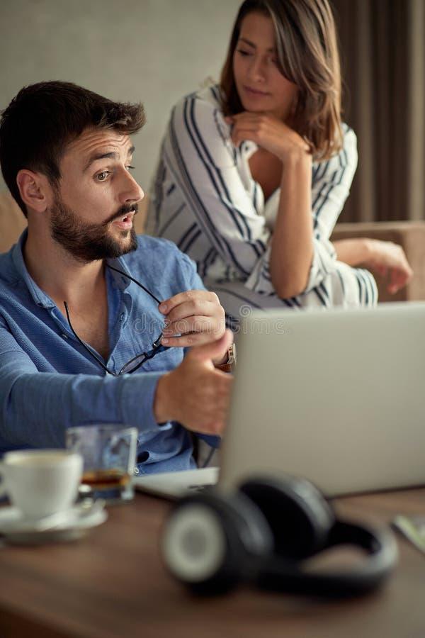 Par med bärbara datorn som tillsammans spenderar tid hemma royaltyfri foto