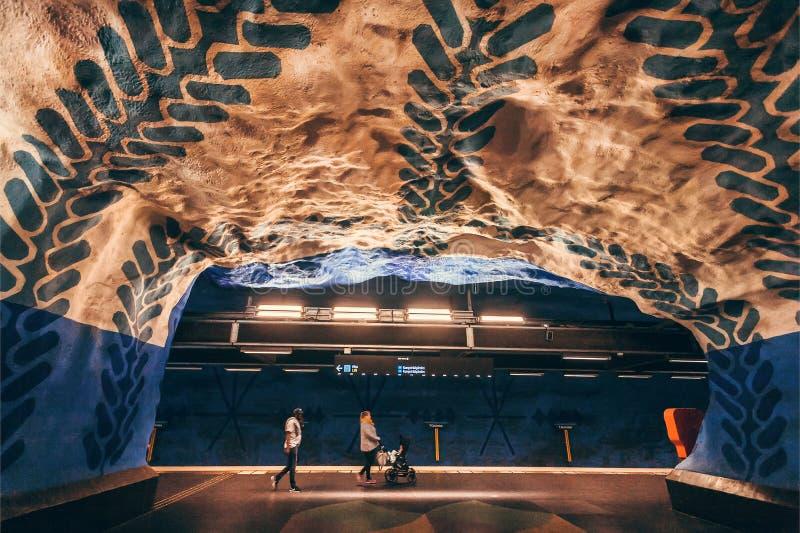 Par med barnvagn i tunnel av den underjordiska stationen med färgrika designväggar royaltyfri foto