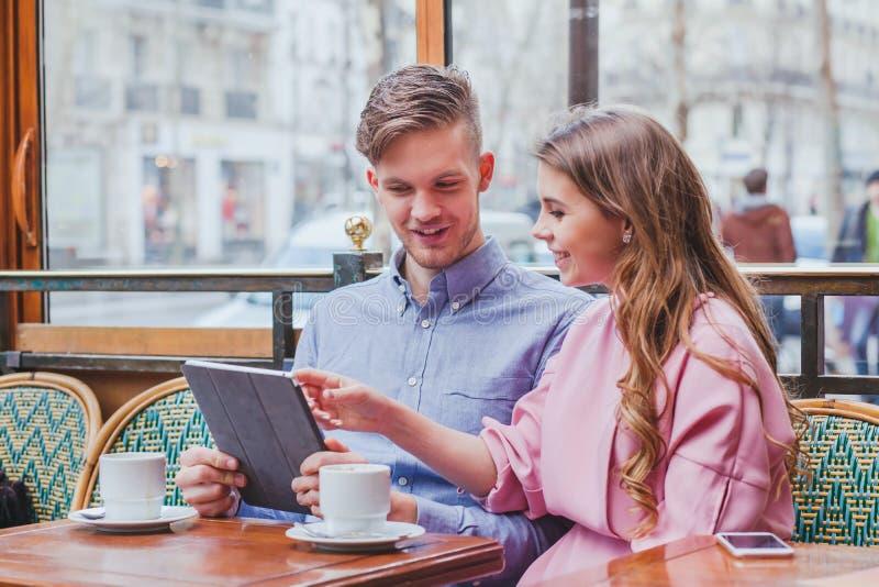 Par med den digitala minnestavlan i kafé royaltyfri bild