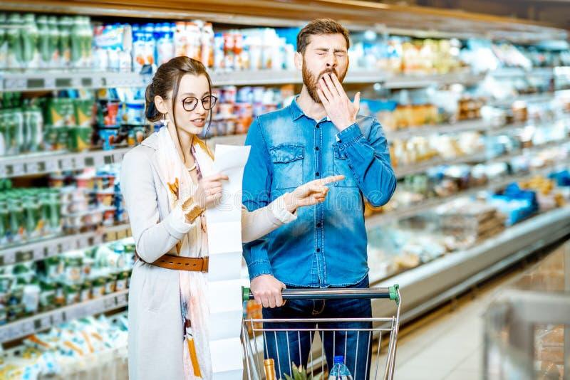 Par med den långa shoppa listan i supermarket arkivfoto