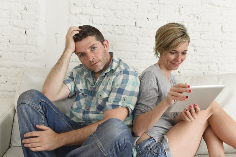 Par med den lyckliga frun som använder internet app på det digitala minnestavlablocket som ignorerar den borrade och ledsna maken royaltyfri bild