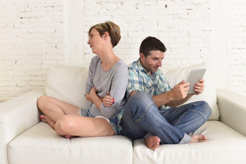Par med den lyckliga maken som använder internet app på det digitala minnestavlablocket som ignorerar den borrade och ledsna frun royaltyfria bilder