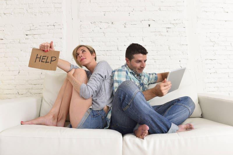 Par med den lyckliga maken som använder internet app på det digitala minnestavlablocket som ignorerar den borrade och ledsna frun arkivfoto