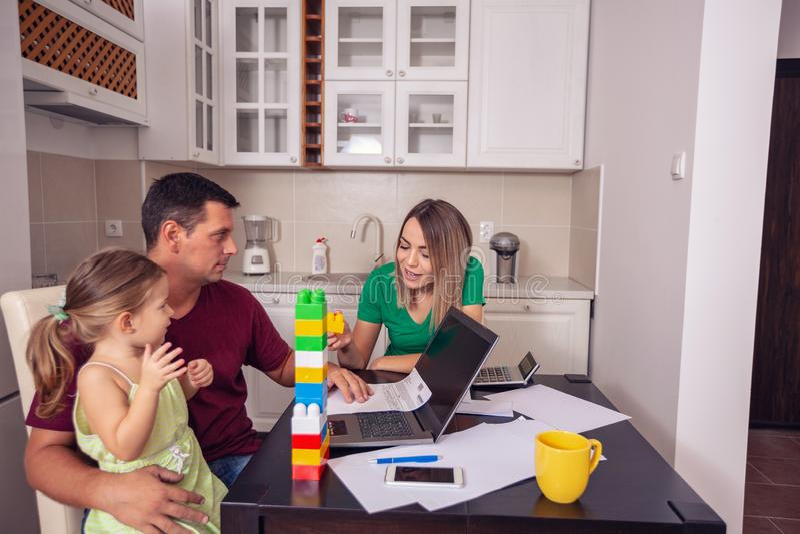 Par med dottern som hemifrån arbetar genom att använda bärbara datorn royaltyfri bild