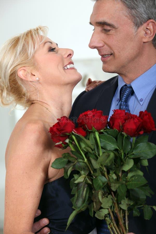 Par med en grupp av rosor arkivbild