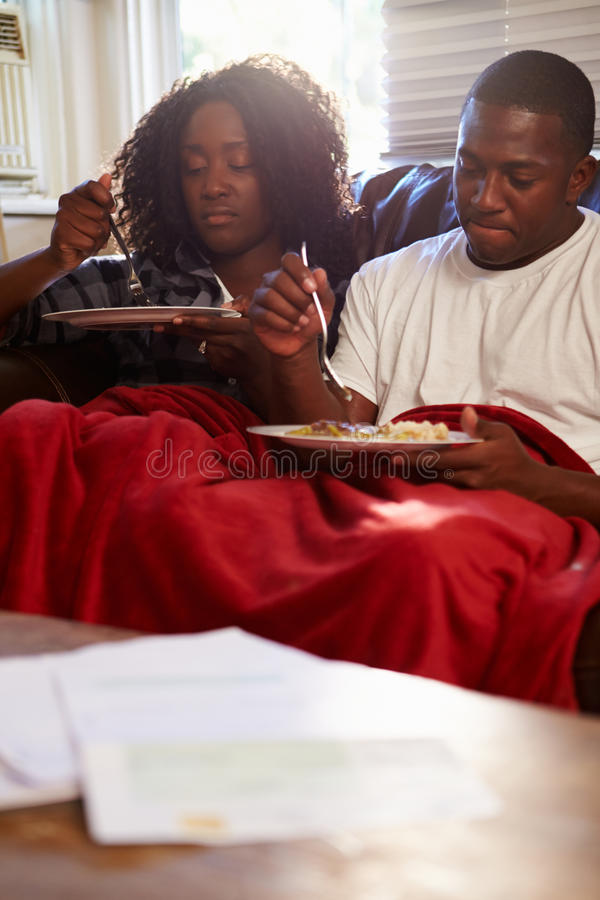 Par med fattigt bantar sammanträde på Sofa Eating Meal royaltyfria foton