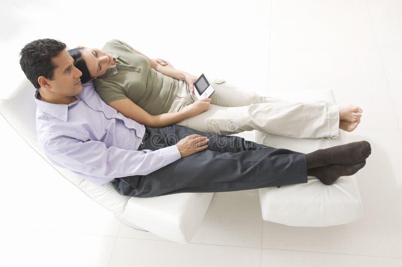 Par med fjärrkontroll som kopplar av på stol fotografering för bildbyråer