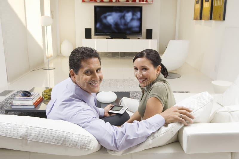 Par med fjärrkontrollsammanträde på soffan royaltyfri foto