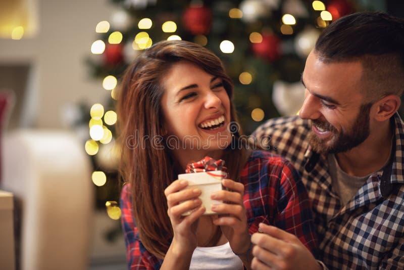 Par med gåvan tillsammans på julhelgdagsafton arkivbilder