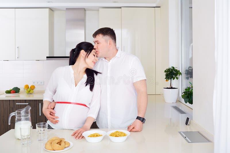 Par med gravida kvinnan som tillsammans kopplar av i kök arkivbild