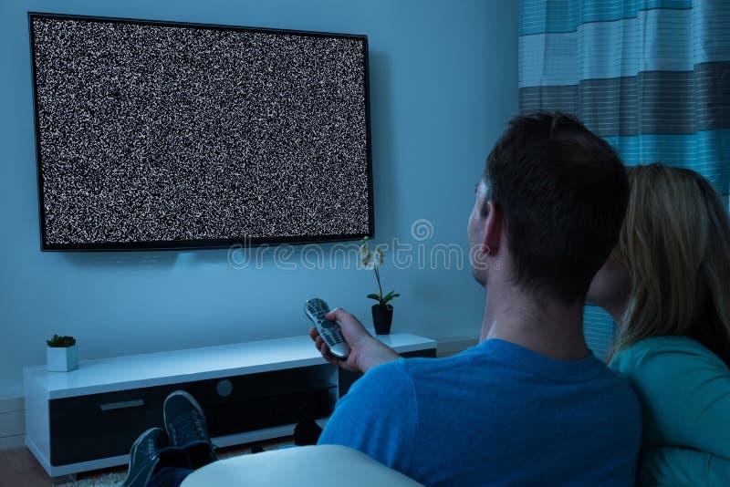 Par med hållande ögonen på television för fjärrkontroll royaltyfri foto
