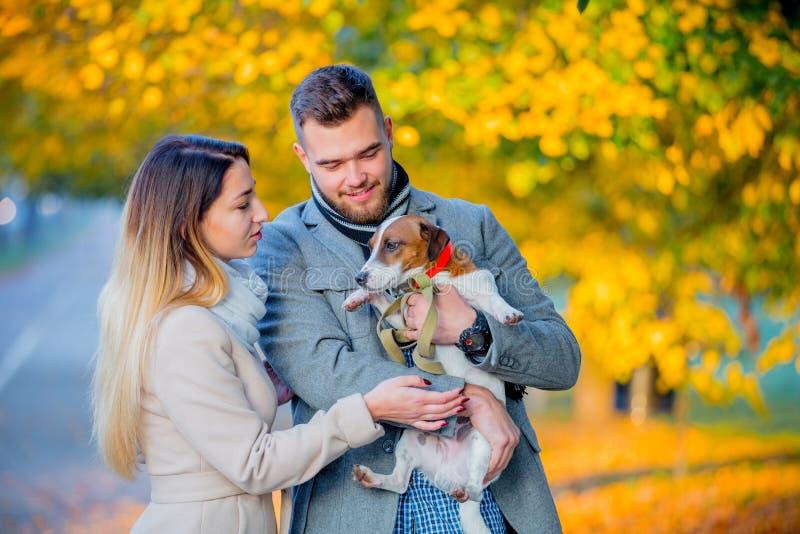 Par med hunden på höstsäsonggränden royaltyfri fotografi