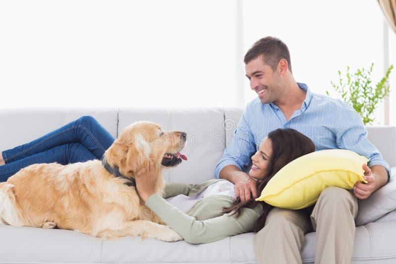 Par med hunden på soffan royaltyfri bild