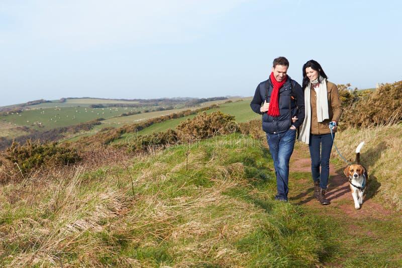 Par med hunden som promenerar den kust- banan arkivbilder