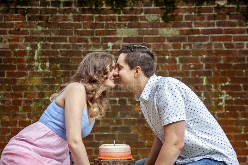 Par med kakan som firar en årsårsdag royaltyfri bild