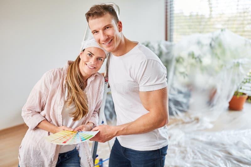 Par med modellen för väggmålarfärg, när renovera arkivfoto