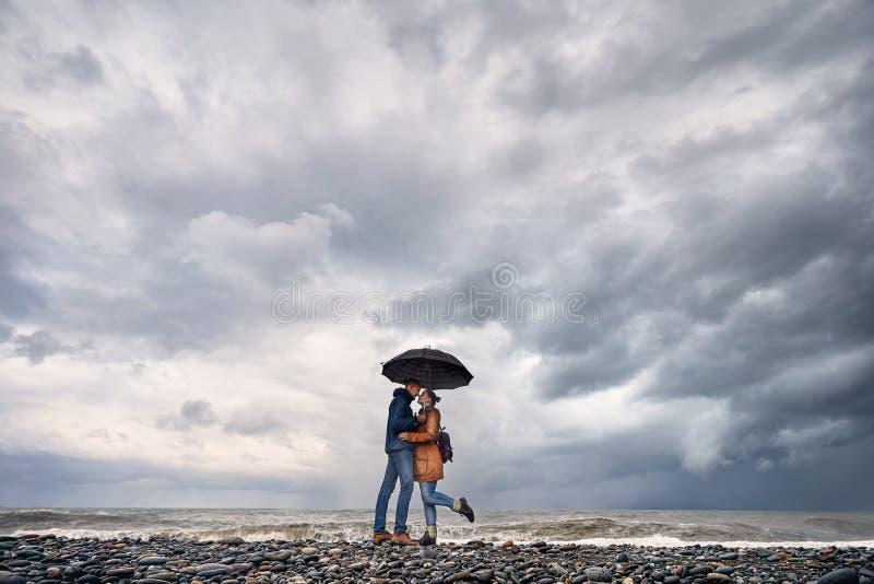 Par med paraplyet nära det stormiga havet arkivfoto