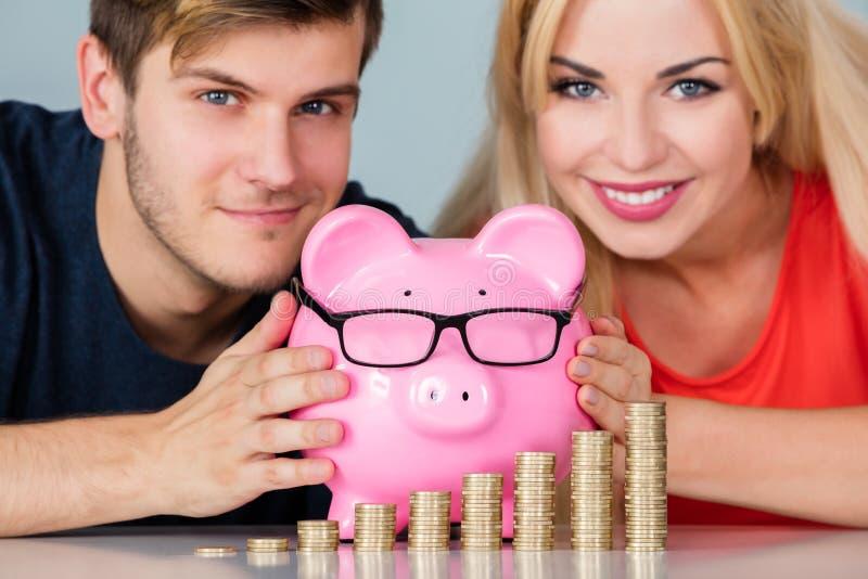 Par med Piggybank och bunten av mynt på skrivbordet arkivfoto